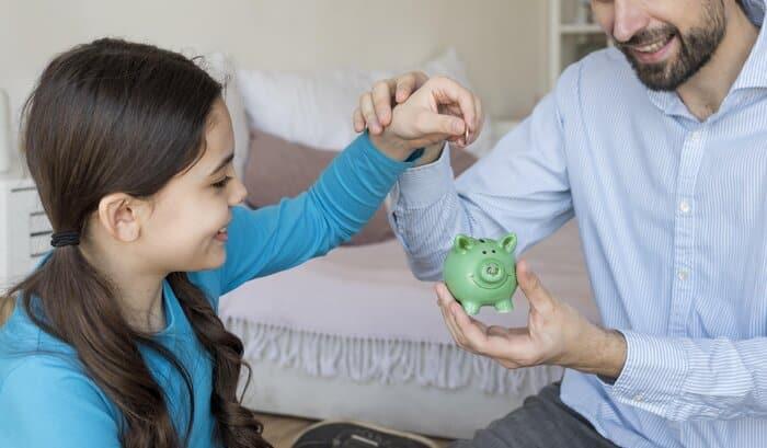 rsz father and daughter putting money in piggy bank Previdência Privada Infantil: tudo o que você precisa saber!